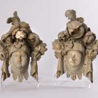 Pair of lacquered wood and formerly gilded heads decorated with bouquets of flowers probably from party room ornaments