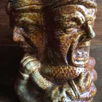 Anthropomorphous sanstone tobacco pot, with esoteric decor in round bump: 4 heads of men and a snake wrapped around their necks