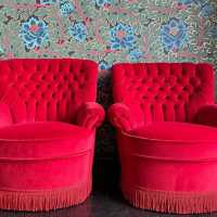 pair red velvet padded armchair