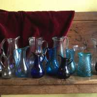 Translucent or colored, from an azure blue to a royal blue, light ocher or garnet going almost to black, these pitchers and decanters are typical of the glassworks of Normandy.
