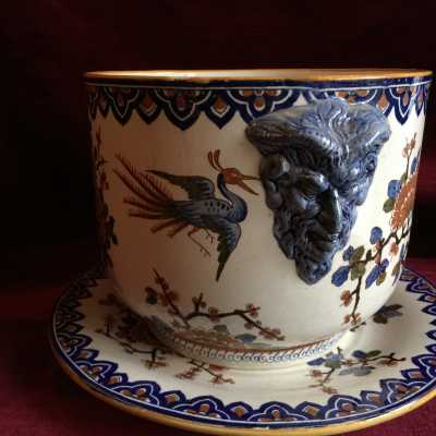 Polychrome decoration of stylized bouquets surrounded by fantastic birds. In half round-bump, on both sides, handle of grip, in blue color: a face of fauna.